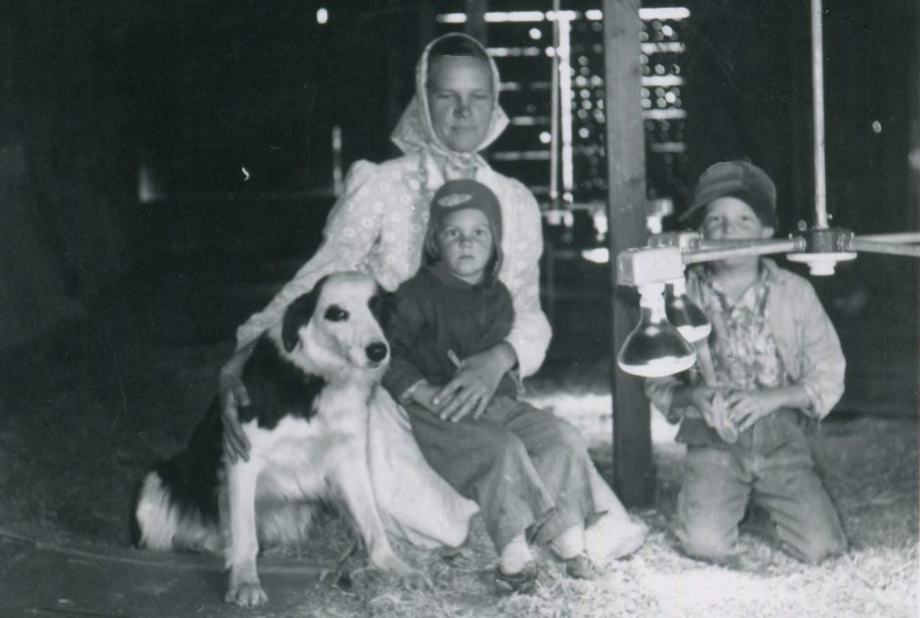 Mom, kids, and dog in barn