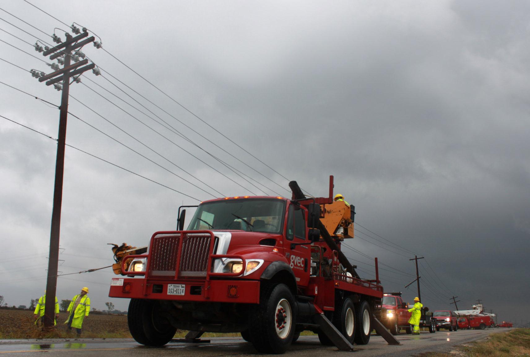 Big truck with lineman repairing lines