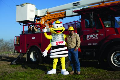 GVEC Louie the Lightening Bug & Lineman Posing in front of GVEC Truck