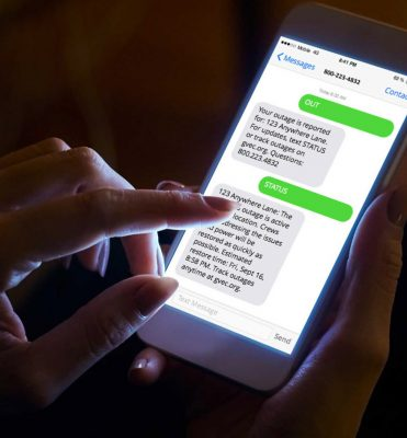 Customer with a smartphone using GVEC TextPower during a power outage