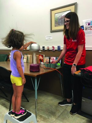 Picture of a student's hair standing on end from touching a Van de Graaff generator at a session of the GVEC Summer Reading Program
